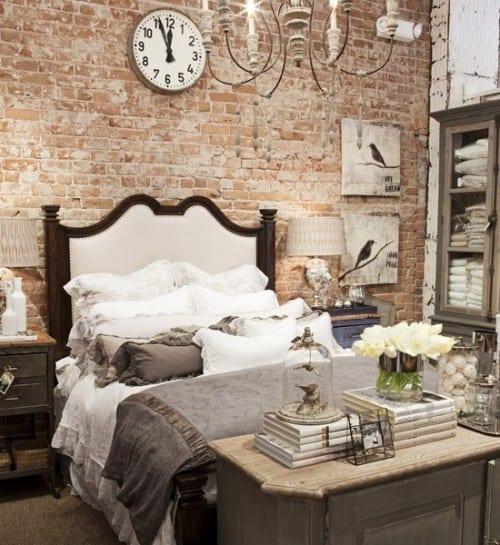 kleines schlafzimmer im shabby chic stil kreativ gestalten mit ziegelwand, wanduhr rund, kerzen-kronleuchter weiß, vintage-bilder mit vögeln und rustikale schlafzimmermöbel in grau