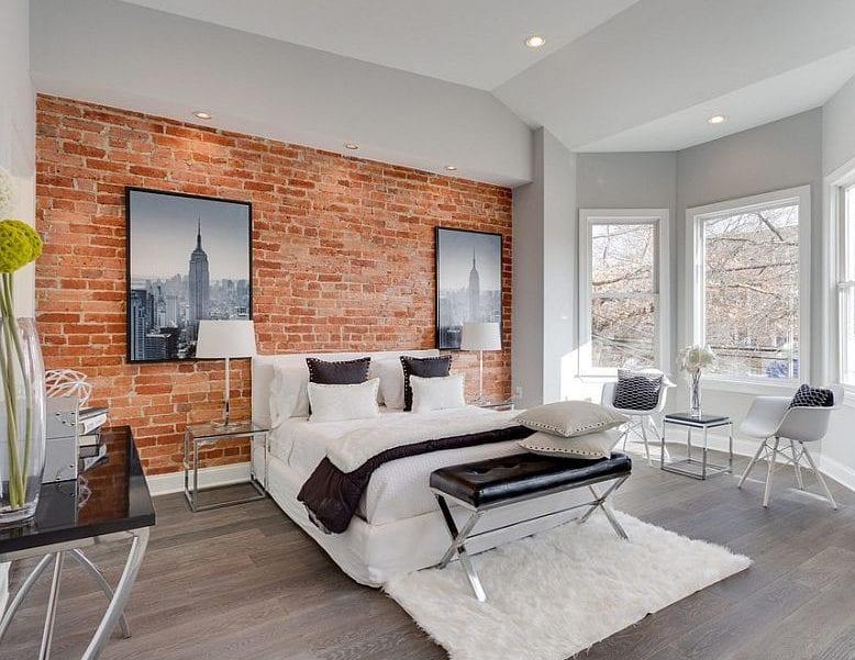 luxuriöses schlafzimmer interieur mit akzentwand aus roten ziegeln, schwarzweißen stadtfotos, weißem box-spring-bett mit schwarzer sitzbank aus leder auf weißem teppich