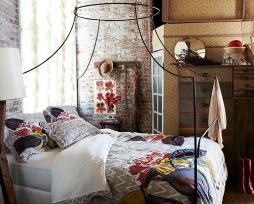 originelle schlafzimmer dekoidee mit ziegelwand, metall-bettrahmen für baldachin, und moderne bettwäsche in weißgrau mit buntem blumenmotiv