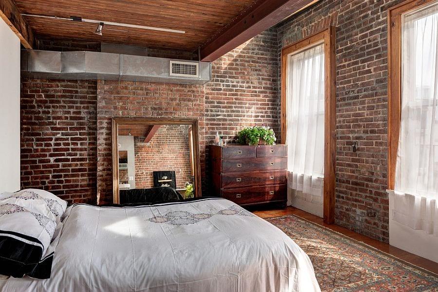 schlafzimmer gemütlich gestalten mit rötlichen ziegeln, holzdecke, vintage kommode aus holz, großem spiegel im rechteckigen spiegelrahmen und Holzrahen mit weißen gardinen