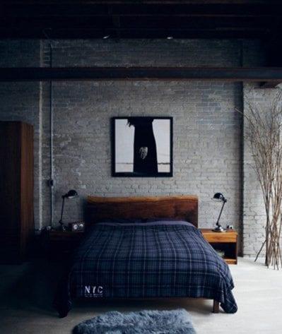 minimalistisches schlafzimmer mit grauer ziegelwand, schwarzweißem bild, holzbett mit holznachttischen und schwarzen tischlampen