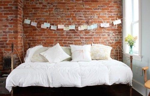 kreative gestaltungsidee schlafzimmer mit ziegelwand aus roten ziegeln, wandfarbe hellblau und holzfensterrahmen weiß und wanddeko mit zetteln und wäscheklammern