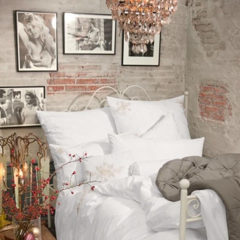 kreative wandgestaltung schlafzimmer mit unverputzten ziegeln und schwarzweißen fotos in schwarzen bilderrahmen