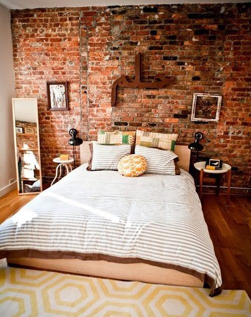 schlafzimmer gestaltung mit ziegelwand, parkett und weißem teppich mit gelbem hexagonmuster, rundem metallhocker und rundem beistelltisch in weiß, vintage wandlampen schwarz und wanddeko mit metallbuchstaben