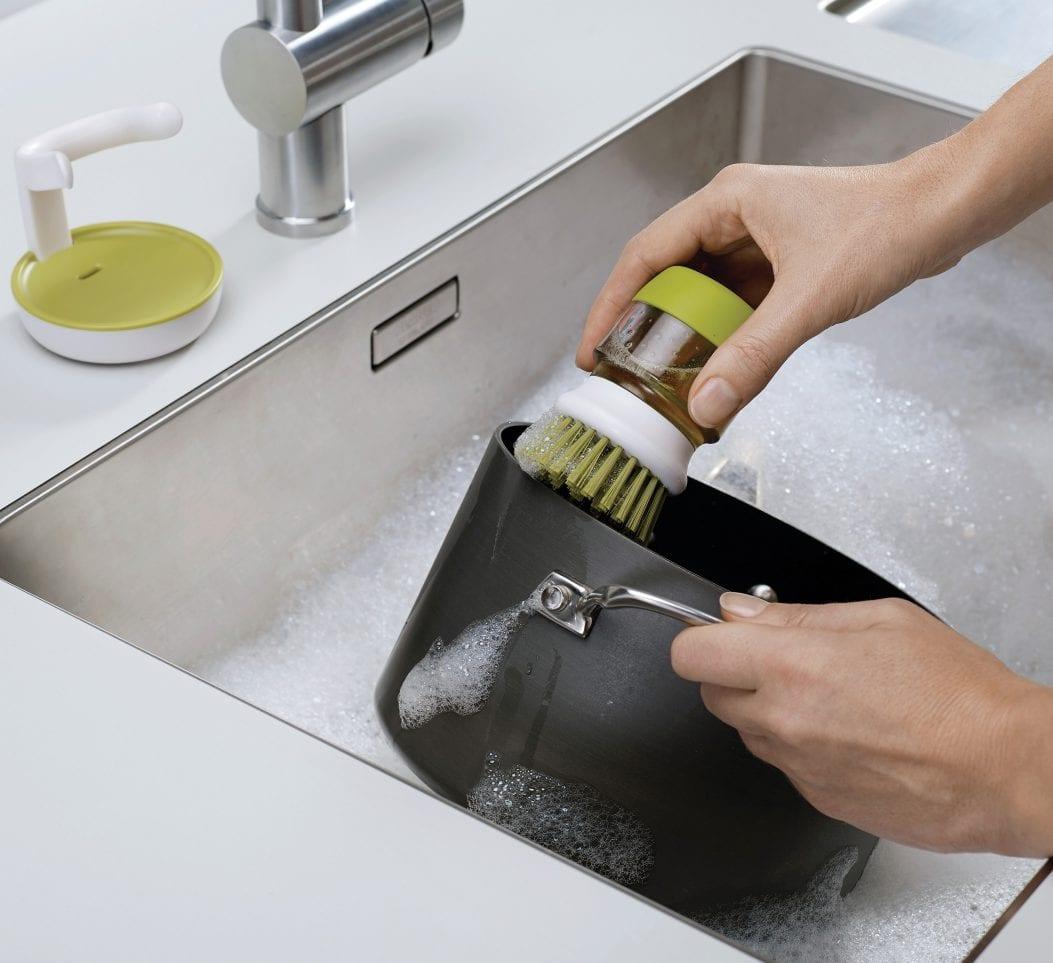 moderne weiß-grüne Spülbürste mit integriertem Seifenspender und Halter für saubere und aufgeräumte küche mit weißer küchenarbeitsplatte