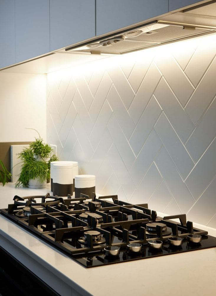 kleine küche mit modernem interieur in weiß mit weißem Fliesenspiegel in fischgrätmuster, schwarzem gaskochfeld und einbauunterschrankleuchte