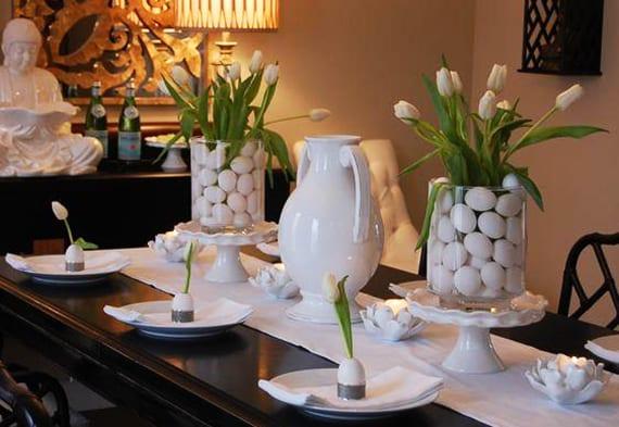 coole dekoidee ostern mit weißen tulpen in runden glasvasen mit weißen eiern und kreative platzteller osterdeko