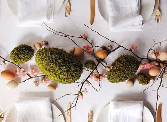 coole ostertischdeko mit diy moos-ostereiern, hartgekochten eiern braun und zweigen mit frühlingsblüten