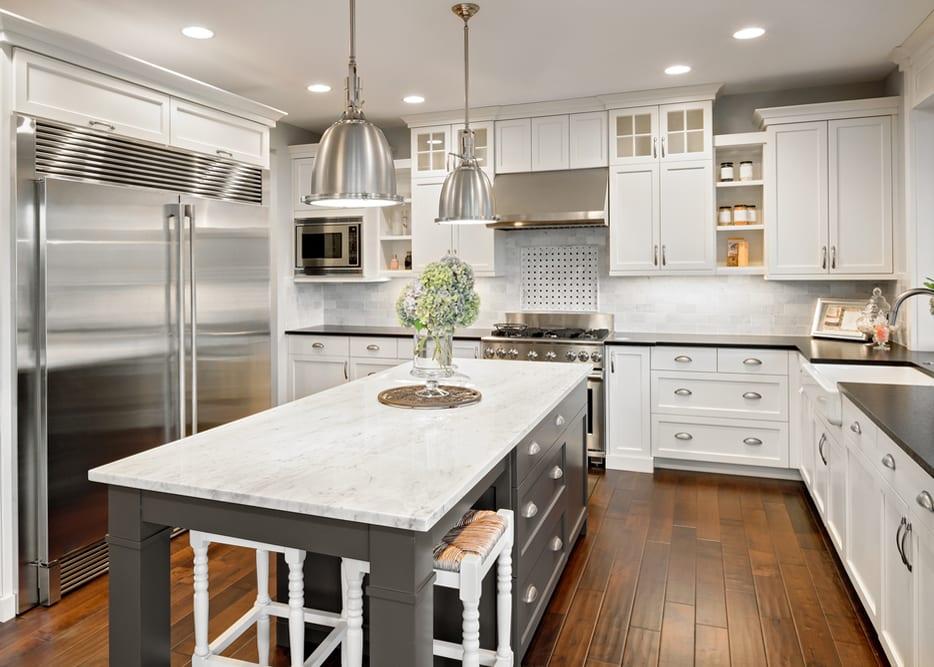 Kochen in sauberem Umfeld_moderne Küche in weiß mit bodenfliesen in Holzoptik, Küchengeräte silber und kochinsel in grau mit marmor arbeitsplatte und vintage-pendellampen