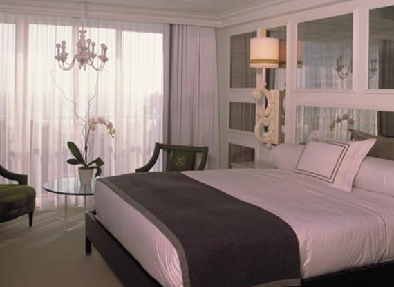 coole Idee für moderne Schlafzimmer gestaltung mit akzentwand aus spigeln, wandleuchten weiß, rundem glastisch mit grünen polstersesseln