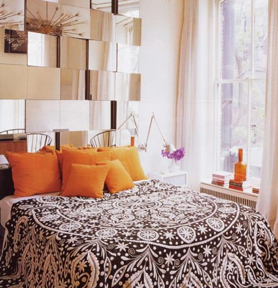 originelle schlafzimmr gestaltung mit kopfbrett aus kleinen spigeln, orangen kissen, schwarzer bettdecke mit weißem muster