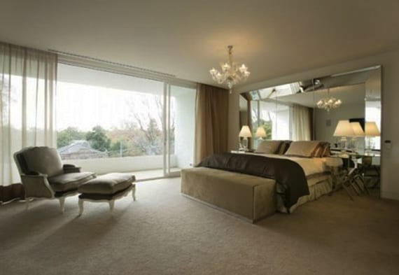 moderne schlafzimmer gestaltungsideen mit spigel als kopfbrett, box-spring-bett, armsessel mit hocker in grau und schiebeturfenstern