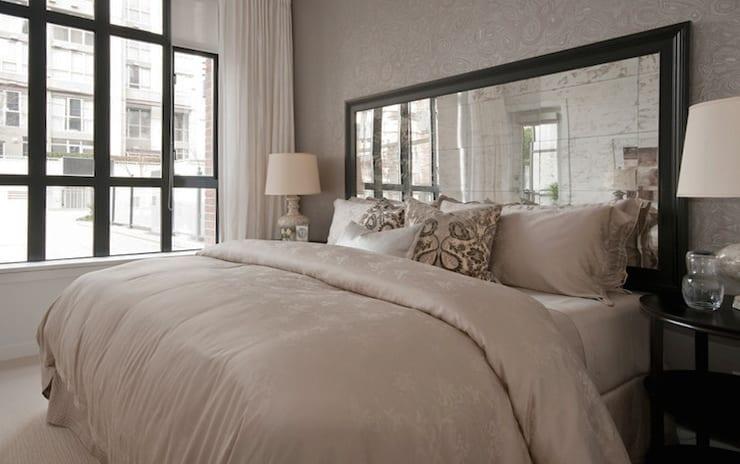 einrichtungsidee für modernes schlafzimmer mit spiegel-kopfteil fürs bett im schwarzen spiegelrahmen, runden nachttische schwarz und luxiöse bettwäsche in Aschenrosa