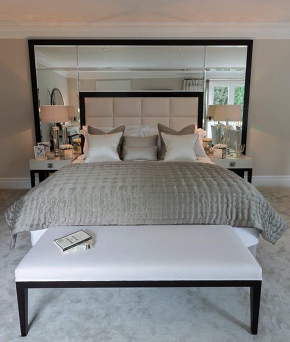 schlafzimmer mit dachschräge modern einrichten mit bett, polsterbank weiß und bett-kopfteil aus weißer Polsterung und Spigel im schearzen rahmen