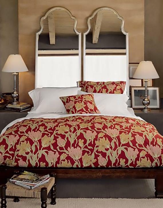 coole schlafzimmer ideen für gemütliche raumgestaltung mit wandfarben beige und grau, roter bettwäsche mit blumenmuster und kreative wanddeko mit spiegeln in silbernen spiegelrahmen