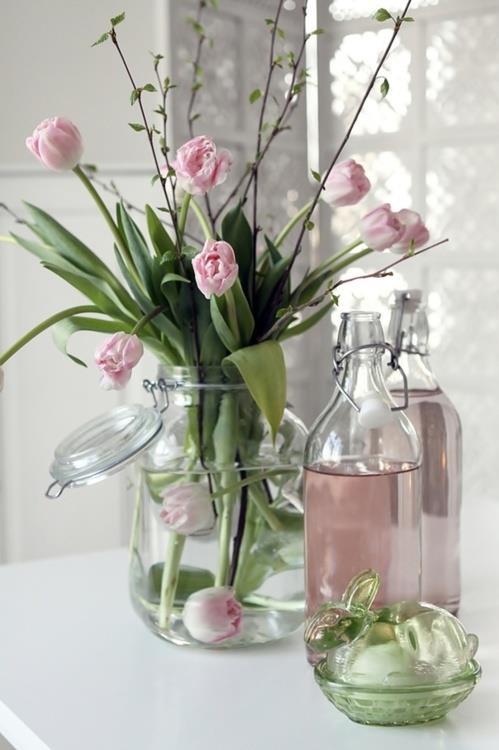 elegante früglingsdeko mit rosafarbigen tulpen in einmachglas und rosafarbigem wasser in glasflasche