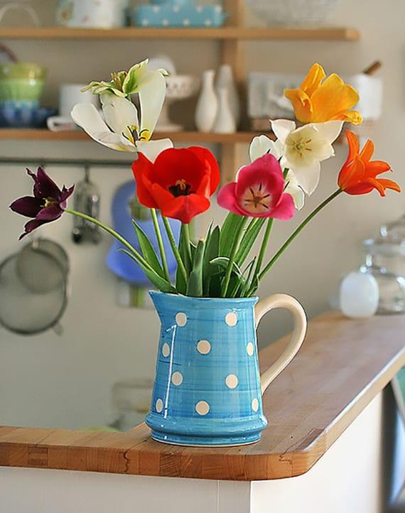 frische raumgestaltung und Blumendeko idee mit bunten tulpen in blauer Kanne mit weißen Punken