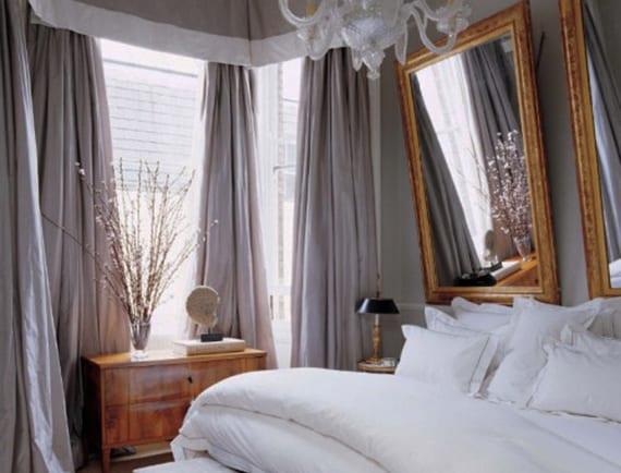 kleines schlafzimmer gestalten mit wandfarbe grau, grauen gardinen, klassischen holzmöbeln und zwei spigeln in goldenen Bilderrahmen hinter dem bett