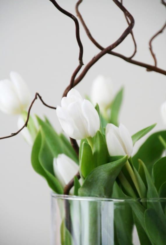 moderne tischdeko mit tulpen und zweigen in glasvase
