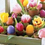 zarte Frühlingsdeko mit Tulpen und Ostereiern in kleinen blumentöpfen mit moos als coole tischdeko idee zum ostern