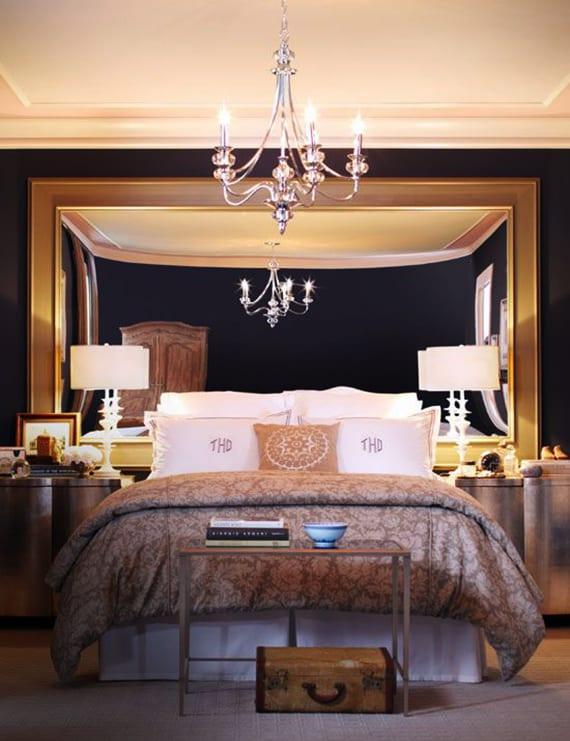 luxus schlafzimmer gestalten in schwarz, weiß und und grau mit großem wandspiegel im goldenem spiegelrahmen als bett kopfteil