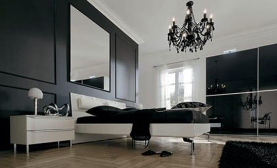 modernes schlafzimmer gestalten mit akzentwand in schwarz, quadratischem Spiegel hinter modernem bett weiß, kleiderschrank mit schiebetüren aus schwarzem glas und neoklassischem kronleuchter schwarz