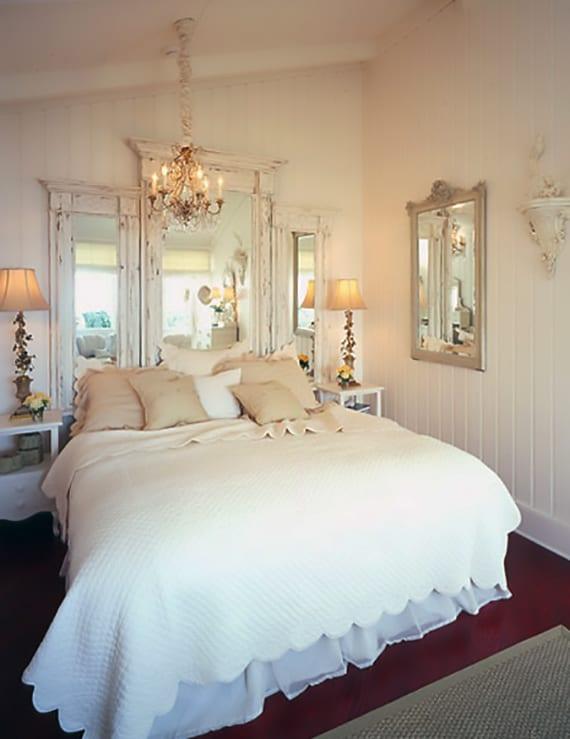 rustikales schlafzimmer interieur mit weißen holzwandpaneelen, kerzen-kronleuchter, rotem teppich, weißen nachttischen holz und wanddeko mit spigeln in weißen holzrahmen