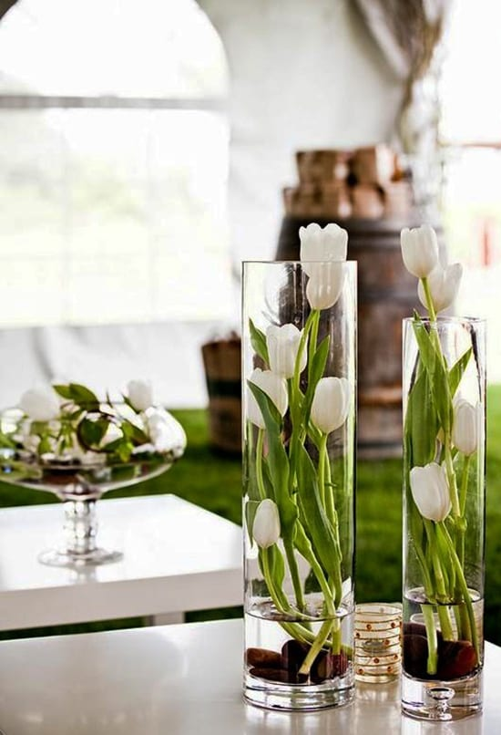 moderne Blumendeko mit Tulpen in runden Glasvasen als tischdeko idee für hochzeiten und feiern im frühling