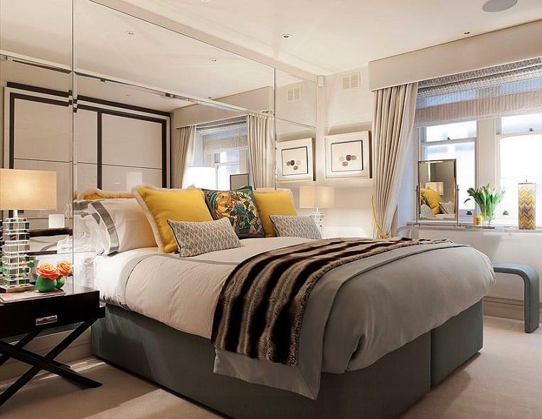 modernes schlafzimmer interieur design mit grauem box-spring-bett,gelben Kissen und weißr bettwäsche, schwarzen nachttischen und spiegelwand