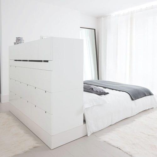 modernes schlafzimmer in weiß mit weißem kommode als bettkopfteil und rautrenner, großem spiegel im schwarzen Rahmen und weißen gardinen und fellteppichen