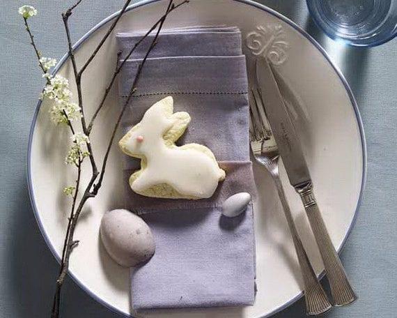 serviette falten zum ostern und platzteller kreativ dekorieren mit osterhase-Plätzchen und frühlingszweig auf blauer stoffserviette