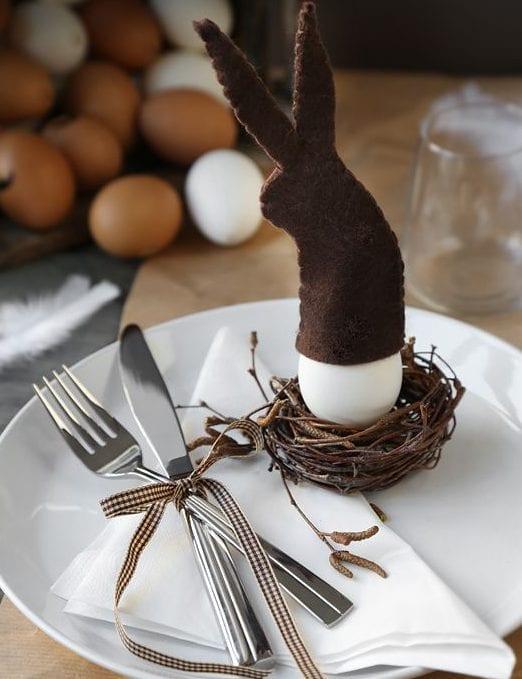 coole ostertischdeko in braun mit Osterei im nest und osterhase-eiwärmer