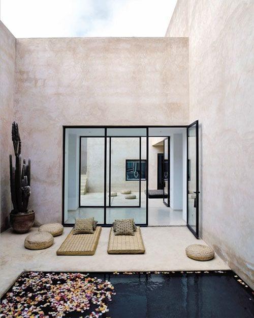 hofgarten mit betonwänden modern gestalten mit glastüren in schwarzen rahmen, polstern in gold und Kaktus im blumentopf