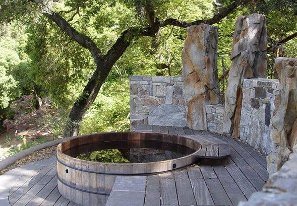 gartengestaltung mit runder badetonne und steinwand als sichtschutz