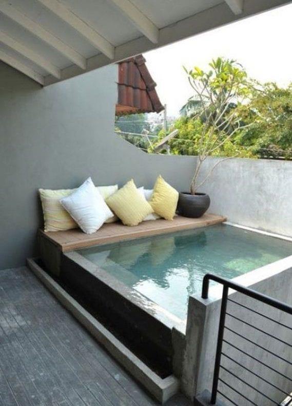 coole terrassengestaltung mit ausgemauertem tauchbecken und holzsitzbank
