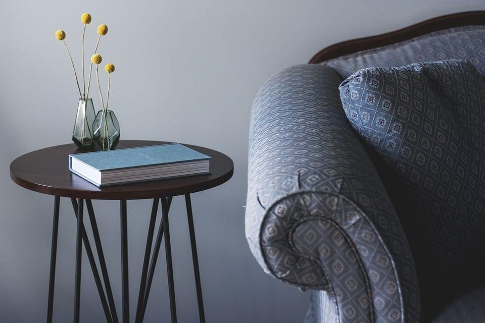 elegante raumgestaltung und dekoration für gästezimmer mit rundem Beistelltisch aus Holz und Metall, frische Blumen in kleinen Glasvasen und Sofa mit gemustertem Damast in blau