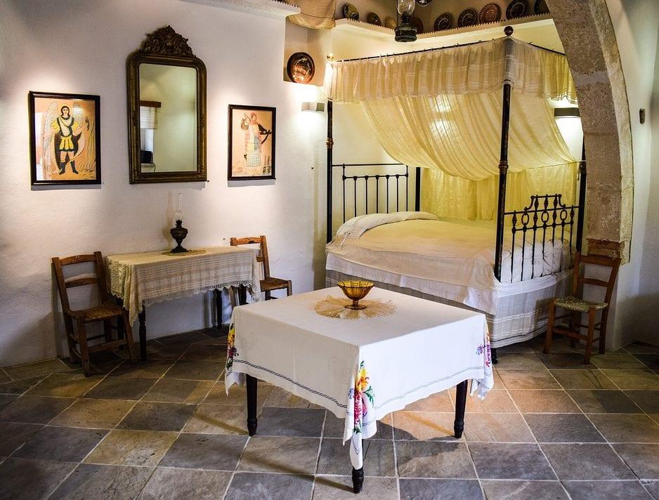 ein gemütliches gästezimmer gestalten mit einem himmelbett, rustikaler Dekoration und passender Beleuchtung