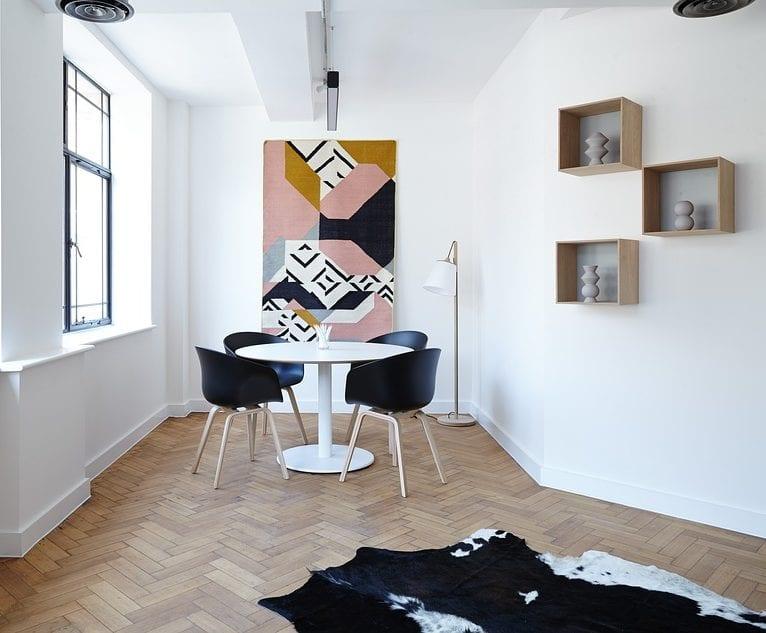 kreative raumgestaltung mit parkett, kuhfell-teppich, rundem esstisch weiß mit schwarzen stühlen und moderne wanddeko mit holzregalen und betonvasen