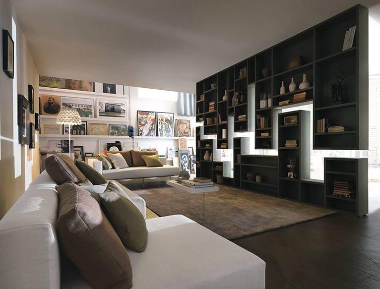 coole raumgestaltung wohnzimmer mit designer bücherregal als raumteiler, moderne Sofa weiß und bunte wanddeko mit gemälden