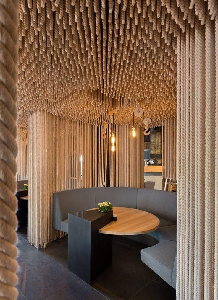 kreative gestaltungsidee mit diy raumteiler aus hängenden seilen für originelle raumteilung in restaurants