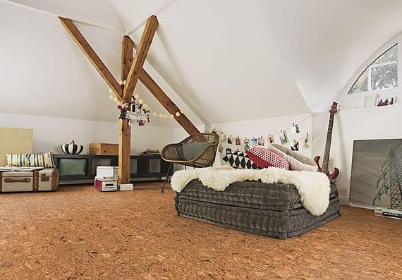 kreative gestaltungsidee mit korkbodenbelag für dachwohnung mit sichtbaren dachkonstruktion aus holz, koffer als beistelltisch und sitzecke aus polstersitzen mit weißem fell-teppich