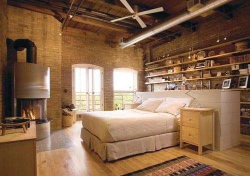 coole gestaltungsidee für schlafzimmer mit ziegelwänden, rundem kamin, wandregalen holz und bett mit nachttischen