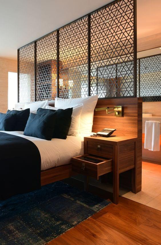 modernes schlafzimmer mit trennwand aus Holz und dekorativen elementen zum offenem bad mit großem wandspiegel