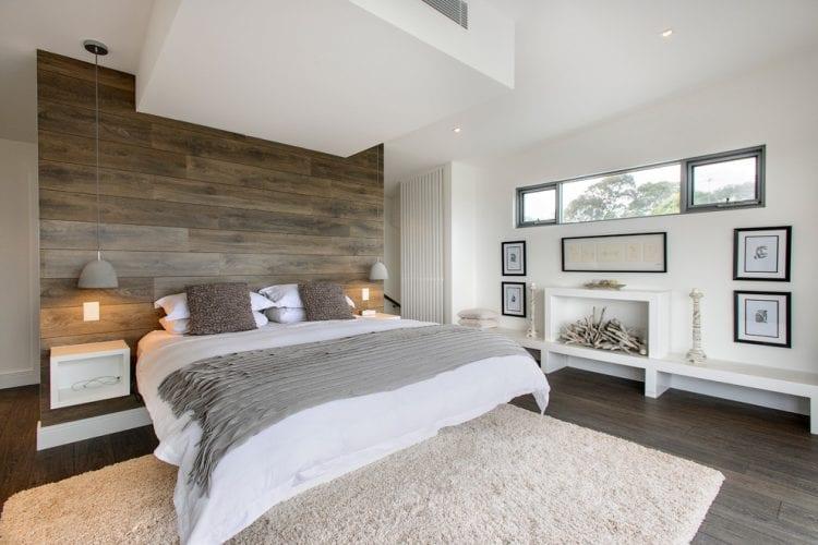 modernes schlafzimmer mit begehbarem kleiderschrank hinter trennwand mit holzverkleidung und badfester über ausgemauerten regal