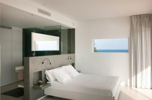 luxuröses schlafzimmer mit offenem bad durch betonwand getrennt
