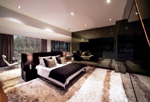 luxuriöses Schlafzimmer mit eingebautem Kleiderschrank im schwarzlack, Bett mit Bettkopfteil und nachttischen auf fellteppich und sitzecke hinterm bett und vor glasfassade