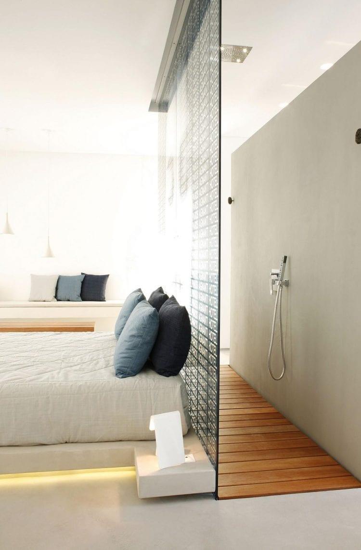 minimalistisches schlafzimmer interior mit poliertem betonboden, indirekter Bettbeleuchtung und Dusche mit holzboden und texturierter Glaswand hinter dem Bett
