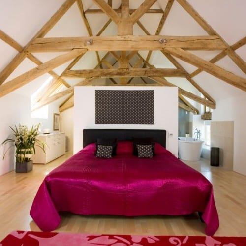 modernes Dachgeschoß-Schlafzimmer mit Holzdachkonstruktion, hellem parkettboden und kleines bad mit badewanne und Kommode hinter Trennwand