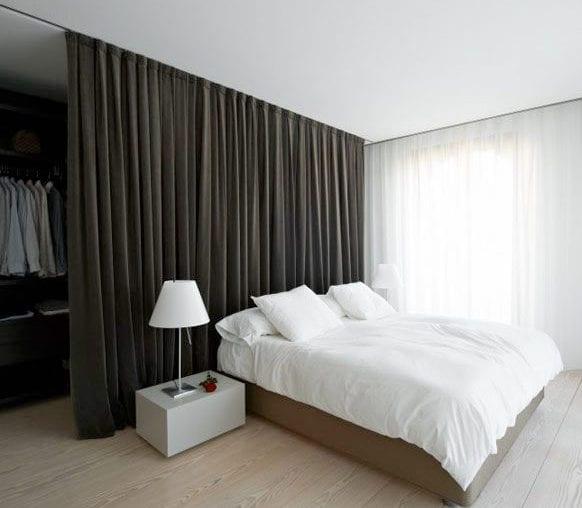 modernes schlafzimmer mit schwarzem Vorhang als Trennung zwischen Garderobe und Bett