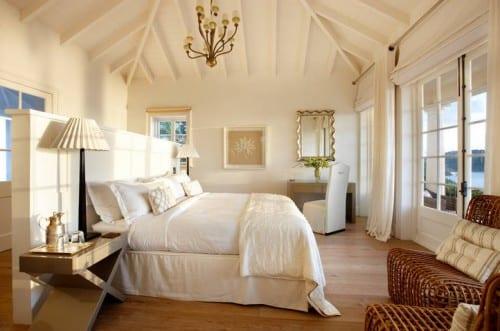 elegantes Interior design für schlafzimmer mit bett in der mitte, schminktisch und kleiner sitzecke mit zwei rattansesseln